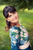 Beautiful happy brunette woman in the park on a warm summer day Stock Images