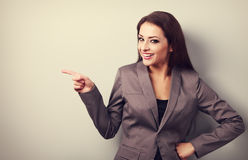 Beautiful happy business woman showing finger on something empty. On copy space background. Toned portrait Stock Images