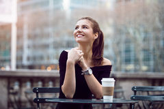 Beautiful happy businesswoman sitting in city park during lunch time or coffee break with paper coffee cup.