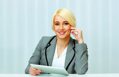Beautiful happy businesswoman sitting at the table with tablet computer Royalty Free Stock Image