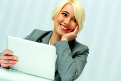 Beautiful happy businesswoman sitting at the table with tablet computer Royalty Free Stock Images