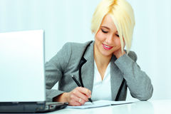 Beautiful happy businesswoman writing in her notebook Stock Images