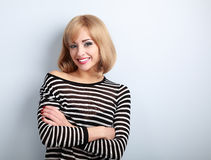 Beautiful happy casual blond woman with folded arms looking with Royalty Free Stock Photography