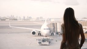 Beautiful happy Caucasian girl with long hair walks up to airport terminal window to enjoy the view of airplanes. Beautiful happy Caucasian girl with long hair stock video footage