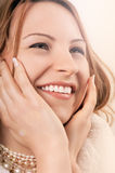 Beautiful happy caucasian woman. Beautiful happy young caucasian woman smiling showing her teeth while holding the face in her hands stock images