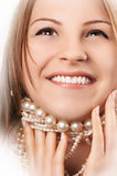 Beautiful happy caucasian woman. Beautiful happy young caucasian woman smiling showing her teeth while playing with pearl necklace royalty free stock image