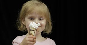 Child with dirty face eats banana with melted chocolate and whipped cream stock footage