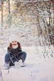 Beautiful happy child girl plays with snow in winter sunny forest Royalty Free Stock Photos