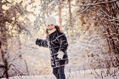 Beautiful happy child girl walking in winter sunny forest Royalty Free Stock Photography