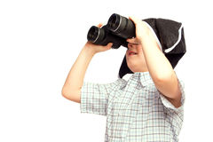 Child in pirate hat looking in binoculars. Beautiful happy child (little boy) in pirate hat looking in binoculars isolated on white background. Search or Stock Image