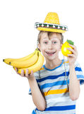 Beautiful happy child in stylish colorful t-shirt holds a bunch of bananas and a fresh lemon. Beautiful funny child in stylish colorful t-shirt and a sombrero Royalty Free Stock Image