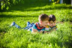 Beautiful happy children, boy brothers, exploring nature with ma. Gnifying glass, summertime. Preschool kids rest in summer holiday camp. Relaxation happy royalty free stock photography