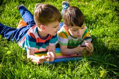 Beautiful happy children, boy brothers, exploring nature with magnifying glass, summertime. Preschool kids rest in summer holiday camp. Relaxation happy royalty free stock photo