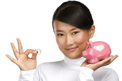 Beautiful happy chinese girl showing a piggybank Royalty Free Stock Photos