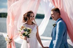 A beautiful and happy couple, the bride and groom, stand on the pier under the wedding arch. Wedding ceremony Royalty Free Stock Image