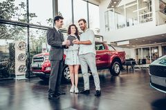Beautiful happy couple buying a car at car salon showroom handsome car salesman showing something on a digital tablet to his stock images