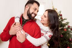 Happy couple at christmastime. Beautiful happy couple hugging and smiling each other at christmastime stock images