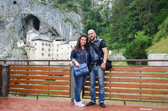 Beautiful happy  couple hugging. Beautiful smiling  tanned bearded muscular men and  handsome brunette with long straight hair hugging near Predjama Castle Royalty Free Stock Photography