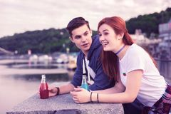 Beautiful happy couple leaning on concrete parapet and having bottles stock photos
