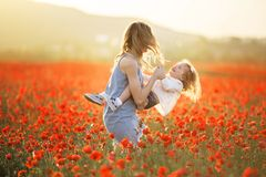 Beautiful smiling child girl with mother are having fun in field of red poppy flowers over sunset lights, spring time. Beautiful happy couple mother and cute royalty free stock image