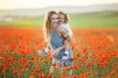 Beautiful smiling baby girl with mother are having fun in field of red poppy flowers over sunset lights, spring time. Beautiful happy couple mother and cute stock images