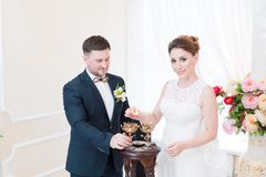 A beautiful happy couple in the registry office performs a wedding ritual with candle lighting. Royalty Free Stock Images