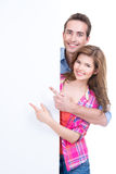 Beautiful happy couple showing at banner. royalty free stock photography