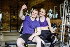 Beautiful happy couple in sports clothes is making selfie using a smart phone and smiling while resting after workout. Royalty Free Stock Image