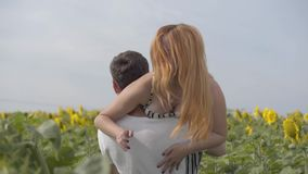 Beautiful happy couple on the sunflower field. The young man throws a girl on his shoulder, she is laughing. Young stock footage