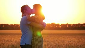 Beautiful happy couple on sunset background. A woman runs to a man standing in a wheat field and kisses him. stock footage
