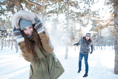 Beautiful happy couple throwing snowballs and having fun Stock Image