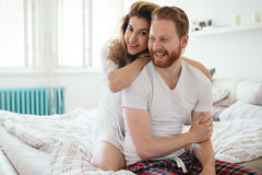 Beautiful happy couple waking up smiling in bedroom. Beautiful happy and romantic  couple waking up smiling in bedroom Royalty Free Stock Images
