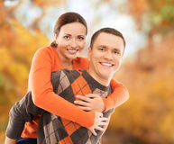 Beautiful and happy couple walking and embracing in the autumn park Royalty Free Stock Photography