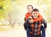 Beautiful and happy couple walking and embracing in the autumn park Royalty Free Stock Photo