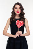 Beautiful happy curly retro styled woman holding heart shaped lollipop Stock Photography
