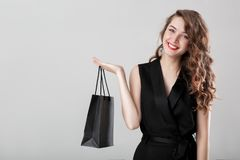 Woman in black with shopping bag. Beautiful happy curly woman in black elegant overall with shopping bag. copy space Royalty Free Stock Photography