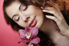 Beautiful happy woman with orchid flower over pink background Royalty Free Stock Images