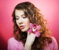 Beautiful happy woman with orchid flower over pink background Stock Photography