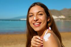 Beautiful happy cute woman applying suntan cream to her nose and shoulder with beach background.  royalty free stock photos
