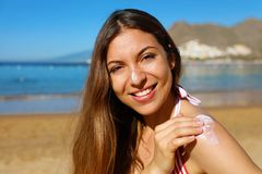 Beautiful happy cute woman applying suntan cream to her nose and shoulder with beach background.  stock photography