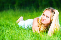 Beautiful happy dreamy woman in summer on nature lying on grass Royalty Free Stock Images