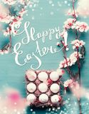 Beautiful Happy Easter greeting card with text lettering. Spring blossom branches frame and egg-crate with Easter eggs at blue royalty free stock photos