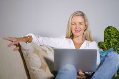Beautiful and happy elegant blond woman early 40s relaxed at home living room using internet on laptop computer working comfortabl stock photo