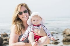Beautiful Happy Expressive Blond Girl Toddler on the Beach with her Grandmother. & Good Sun Protection in Mexico Royalty Free Stock Photography