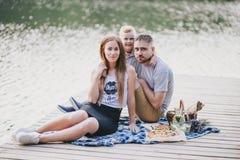 Beautiful happy family having picnic near lake Stock Photography