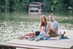 Beautiful happy family having picnic near lake Royalty Free Stock Photography