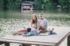 Beautiful happy family having picnic near lake Royalty Free Stock Image