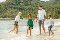 beautiful happy family on vacation playing with water stock images