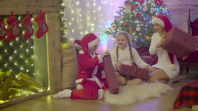 Beautiful happy family wearing santa hat and exchanging Christmas gifts at home stock footage