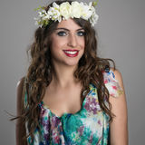 Beautiful happy fantasy girl with flowers in her head posing at camera. With toothy smile Royalty Free Stock Photo
